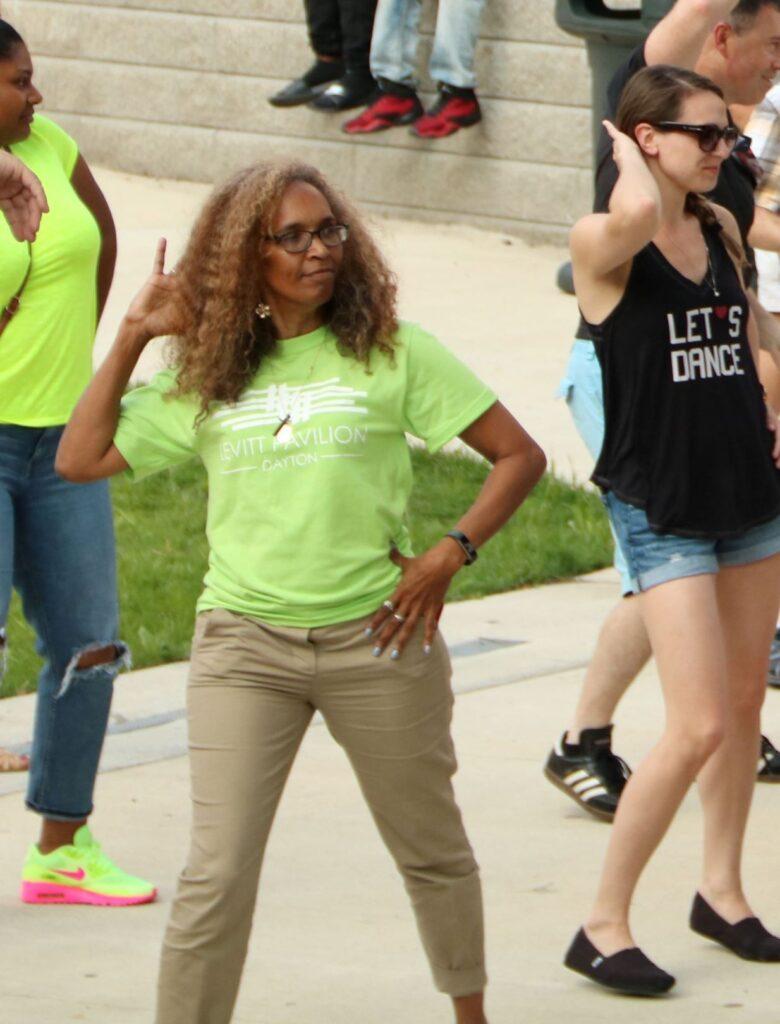 Volunteer in bright green t-shirt dances on concrete dancefloor as part of salsa class.